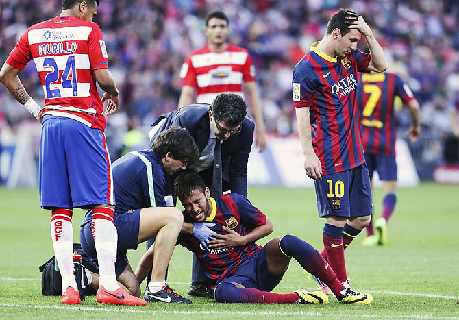 Barcelona's Neymar is helped by the medical staff next to Lionel Messi (right) on Saturday