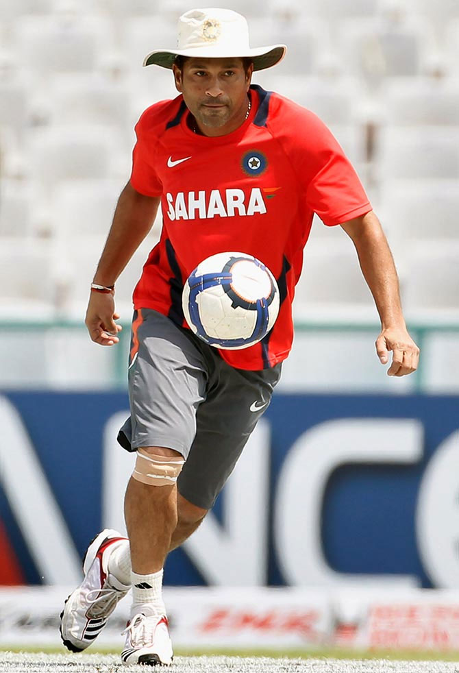 Sachin Tendulkar plays football during a training session