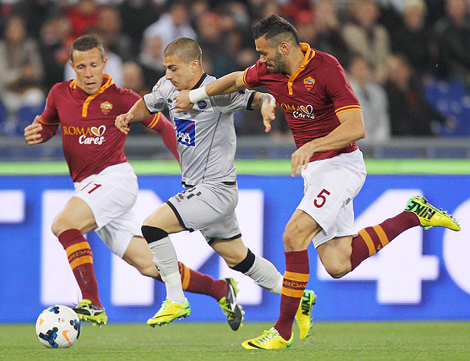 Rodrigo Taddei (left) and Leandro Castan (right) of AS Roma vie for possession agianst Giuseppe De Luca of Atalanta during their Serie A match at Stadio Olimpico in Rome on Saturday