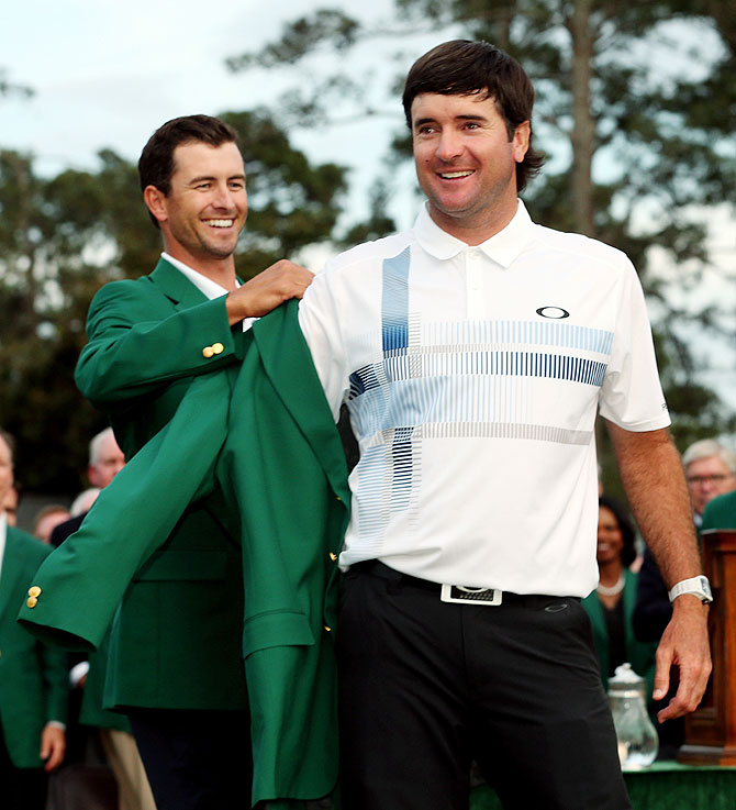 Adam Scott of Australia (left) presents Bubba Watson of the United States with the green jacket after Watson won the 2014 Masters Tournament on Sunday