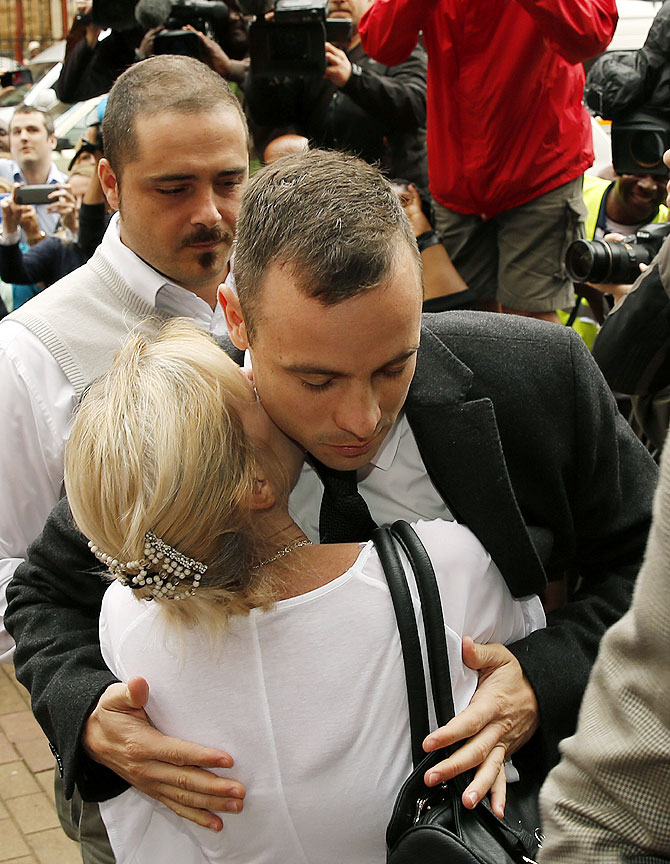 Olympic and Paralympic track star Oscar Pistorius (right) is hugged by a supporter as he arrives ahead of his trial for the murder of his girlfriend Reeva Steenkamp at the North Gauteng High Court in Pretoria on Monday