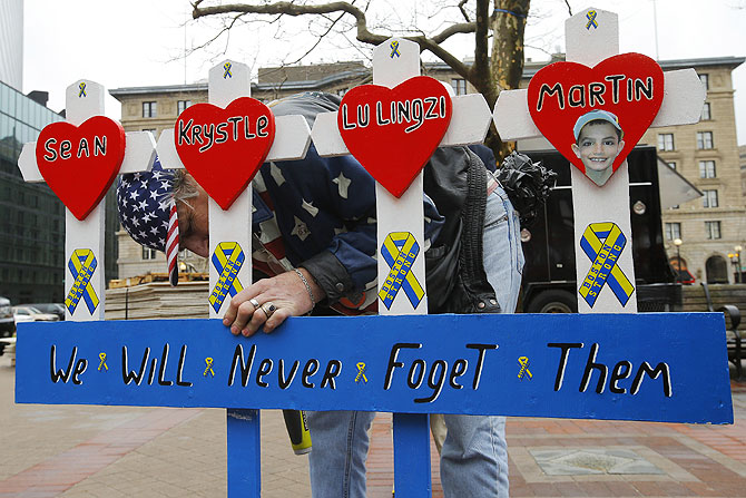 Kevin Brown puts up a hand made memorial for victims of the 2013 Boston Marathon bombings near the race's finish line in Boston, Massachusetts on Tuesday, marking the one year anniversary of the bombings