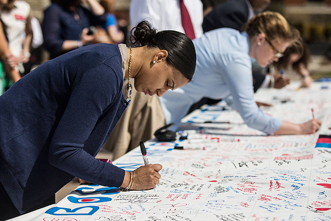 A woman writes a tribute on a memorial before a flag raising ceremony at Boston Medical Center to commemorate the one year anniversary of the Boston marathon bombings on Tuesday