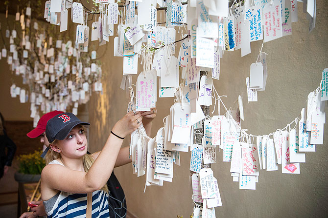 Kathryn Shea, from Rochester, New York, hangs a hand-written message she wrote on a tree hung with messages inside a display titled, 'Dear Boston: Messages from the Marathon Memorial' in the Boston Public Library to commemorate the 2013 Boston Maraton bombings, on Tuesday