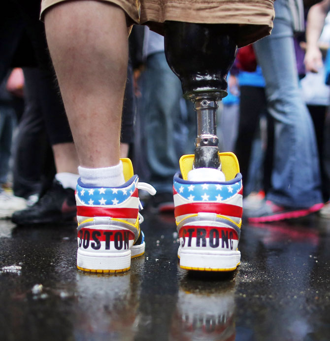 The shoes of 2013 Boston Marathon bombing survivor J.P. Norden read 'Boston Strong' as he stands at the finish line on the one-year anniversary of the bombings in Boston, Massachusetts on Tuesday. J.P. and his brother Paul, also a bombing survivor, took part in the final portion of the 'Legs for Life Relay', joining family members and friends who walked the entire Marathon route to raise money for children needing prosthetic limbs.