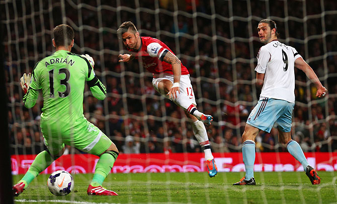 Olivier Giroud of Arsenal shoots past Adrian of West Ham United (13) to score as Andy Carroll of West Ham United (9) looks on