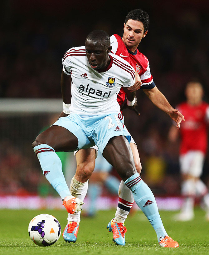 Mohamed Diame of West Ham United holds off a challenge by Mikel Arteta of Arsenal (right)