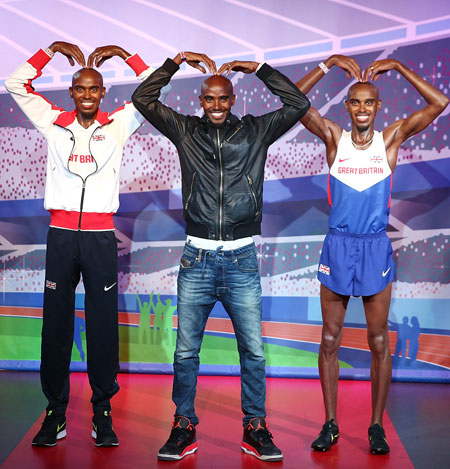 Mo Farah (center) poses for a photocall to unveil his two waxworks