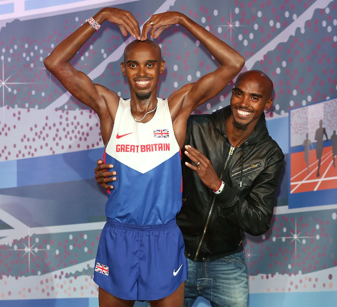Mo Farah poses for a photocall to unveil his two waxworks