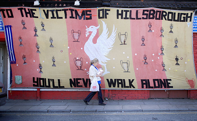 A woman walks past a Hillsborough tribute banner as fans arrive in Anfield for a memorial service marking the 25th anniversary of the Hillsborough Disaster at Anfield stadium in Liverpool, on Tuesday