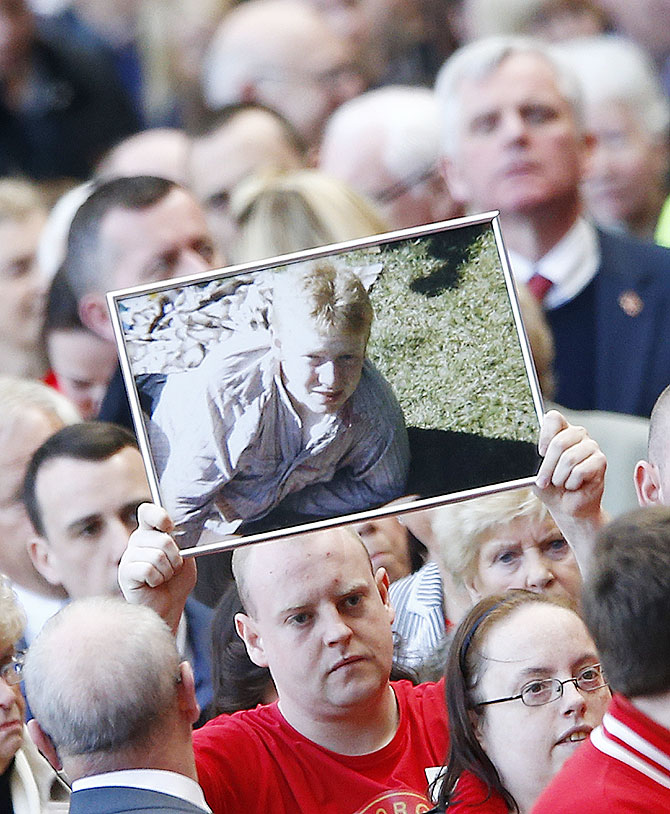 A man holds up a picture of a victim during a memorial service to mark the 25th anniversary of the Hillsborough disaster at Anfield on Tuesday