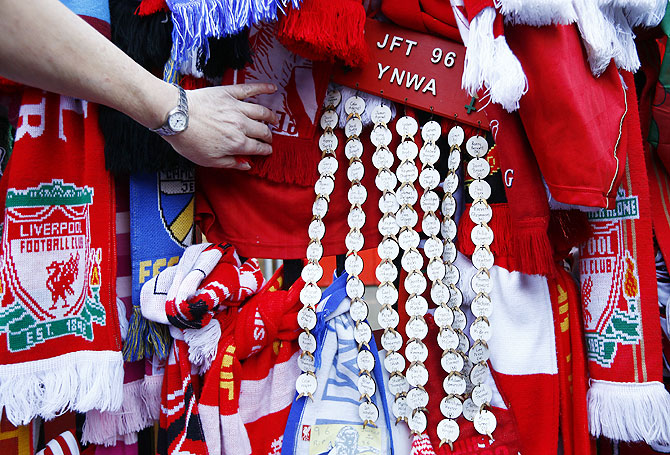 A fan looks at scarves placed as tributes on the Shankly gates before a memorial service to mark the 25th anniversary of the Hillsborough disaster at Anfield on Tuesday