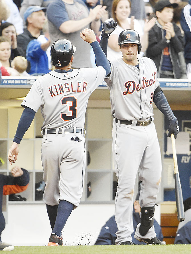 Ian Kinsler #3 of the Detroit Tigers is congratulated by Nick Castellanos #9 after scoring