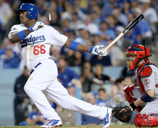 Yasiel Puig of the Los Angeles Dodgers hits a broken bat single