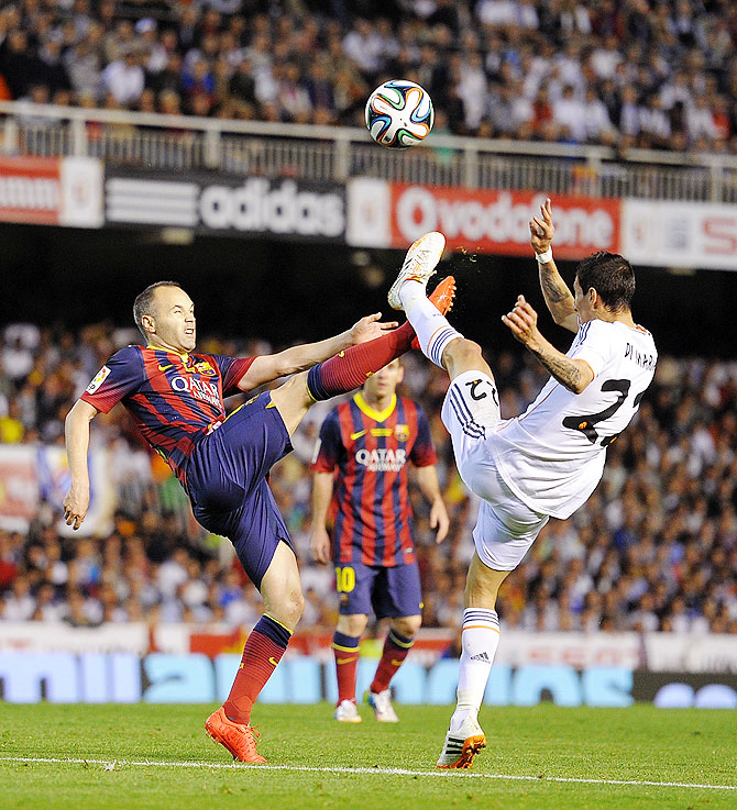 Andres Iniesta (left) of FC Barcelona battles for the ball with Angel Di Maria of Real Madrid on Wednesday