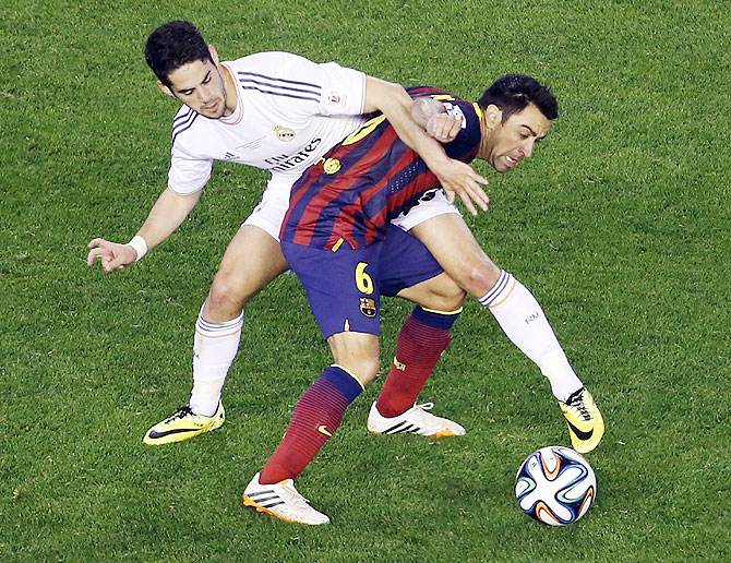 Barcelona's Xavi Hernandez (right) gets entangled with Real Madrid's Isco as they vie for possession on Wednesday