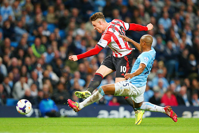 Connor Wickham of Sunderland beats Fernandinho of Manchester City to score the second goal during their English Premier League match at Etihad Stadium in Manchester on Wednesday