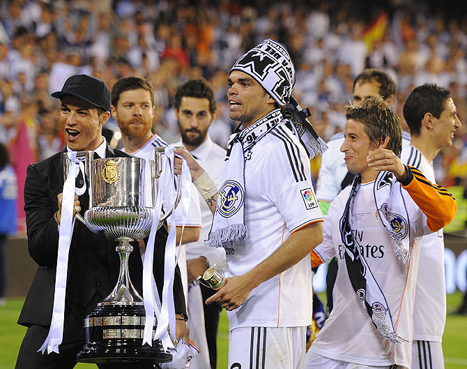 Cristiano Ronaldo, Pepe and Fabio Coentrao hold the Copa del Rey trophy after beating Barcelona at Estadio Mestalla in Valencia on Wednesday