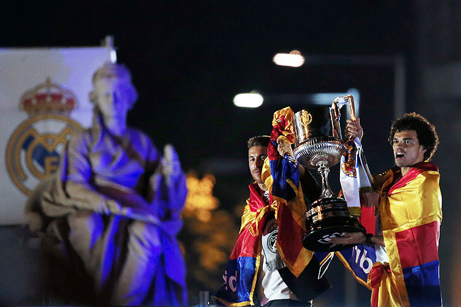 Real Madrid's players Sergio Ramos (left) and Pepe hold the King's Cup trophy at Cibeles fountain during celebrations in central Madrid on Thursday