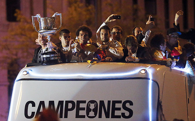 Real Madrid players celebrate winning the King's Cup on top of a bus as they arrive at Cibeles fountain in Madrid on Thursday