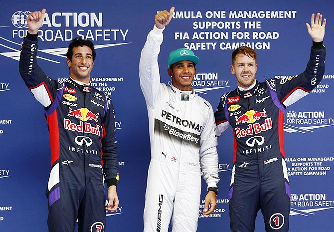 Mercedes Formula One driver Lewis Hamilton (centre) celebrates after taking pole position at the qualifying session of the Chinese F1 Grand Prix, with Red Bull's Daniel Ricciardo (left) and  Sebastian Vettel in a rainswept Chinese Grand Prix qualifying on Saturday