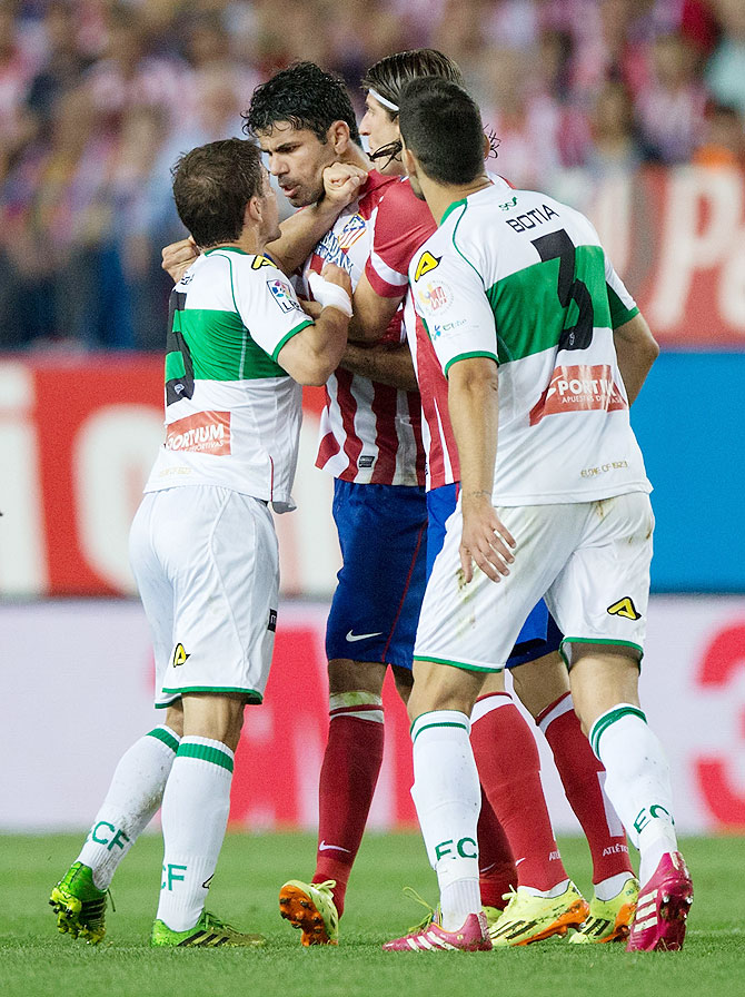 Diego Costa (2nd from left) of Atletico de Madrid argues with Alberto Rivera (left) and Alberto Tomas Botia (right) of Elche FC during their La Liga match at Vicente Calderon Stadium in Madrid on Friday