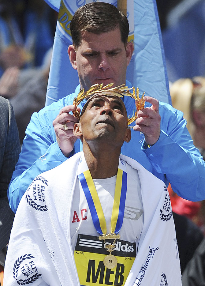 Meb Keflezighi of the U.S. receives the his garland after winning the men's division at the 118th Boston Marathon on Monday