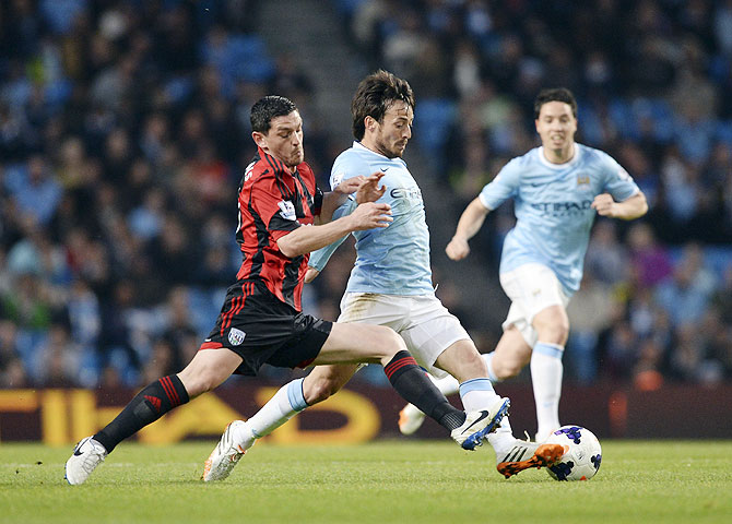 Manchester City's David Silva (centre) challenges West Bromwich Albion's Graham Dorrans during their English Premier League match at the Etihad stadium in Manchester on Monday