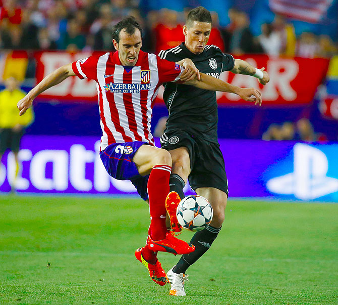 Atletico Madrid's Diego Godin (left) challenges Chelsea's Fernando Torres (right) during their Champions League semi-final first leg match at Vicente Calderon stadium in Madr
