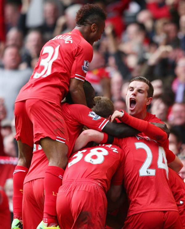 Philippe Coutinho of Liverpool is mobbed by team-mates after scoring the third goal during the Barclays Premier League match against Manchester City at Anfield on April 13.