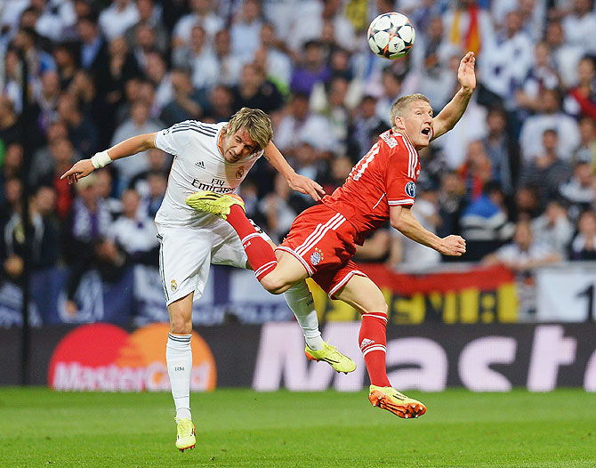 Bastian Schweinsteiger of Bayern Munich is challenged by Fabio Coentrao of Real Madrid during their Champions League semi-final first leg match on Wednesday