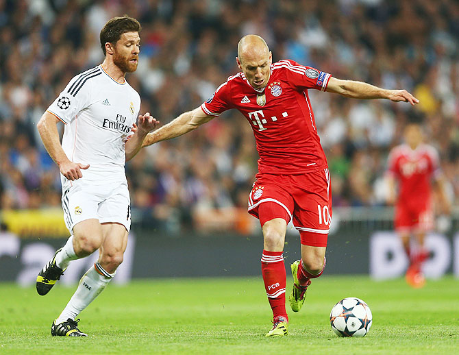 Arjen Robben of Bayern Munich is challenged by Xabi Alonso of Real Madrid during the UEFA Champions League semi-final first leg match on Wednesday
