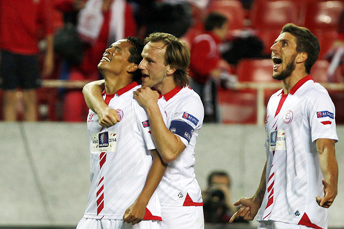 Sevilla's Carlos Bacca (left) celebrates with teammates Ivan Rakitic (centre) and Daniel Carrico after scoring against Valencia during their Europa League semi-final first leg match at Ramon Sanchez Pizjuan stadium in Seville on Thursday