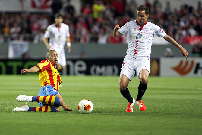 Valencia's Sofiane Feghouli (left) and Sevilla's Fernando Navarro fight for the ball during their Europa League semi-final first leg match at Ramon Sanchez Pizjuan stadium in Seville on Thursday