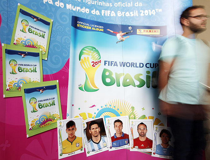 A man walks past the banner of the official 2014 FIFA World Cup sticker album in Sao Paulo