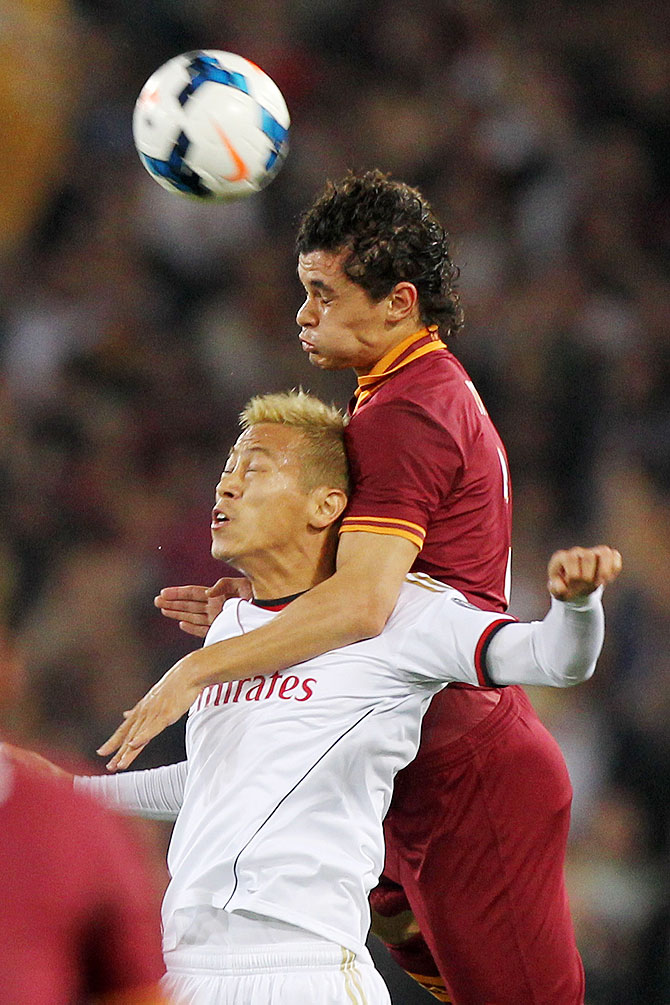 Keisuke Honda (left) of AC Milan competes for the ball with Dodo of AS Roma during the Serie A match at Stadio Olimpico in Rome, Italy on Friday
