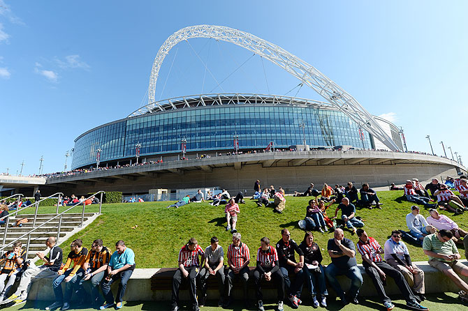 Football fans sit on the grass outside Wembley stadium