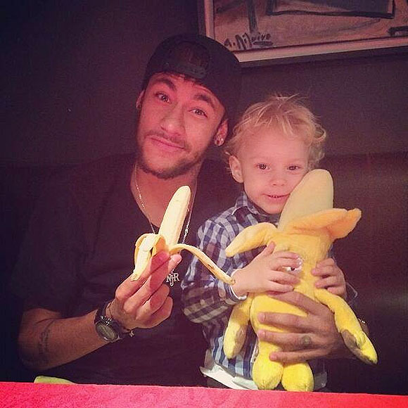 Neymar and his two-year-old son David Lucca da Silva Santos eat a banana as they pose on Tuesday
