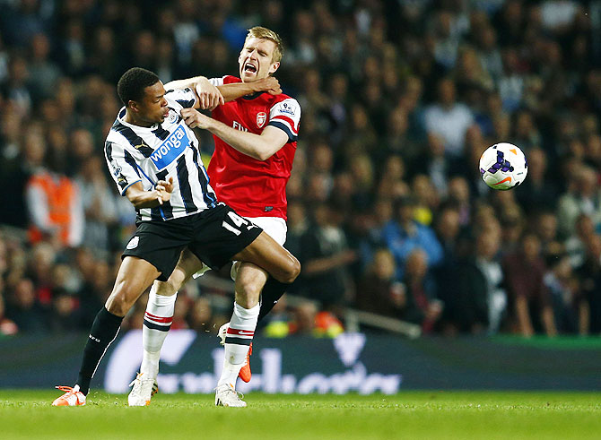 Arsenal's Per Mertesacker (right) is challenged by Newcastle United's Loic Remy during their English Premier League match  on Monday
