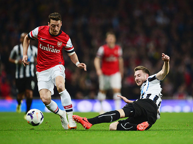 Paul Dummett of Newcastle United tackles Mesut Ozil of Arsenal during their English Premier League match at Emirates Stadium on Monday