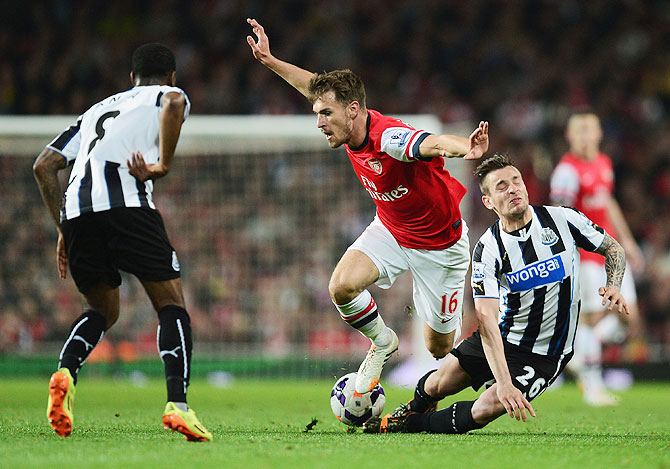 Aaron Ramsey of Arsenal takes on Vurnon Anita (left) and Mathieu Debuchy of Newcastle United (right) during their English Premier League match at Emirates Stadium on Monday