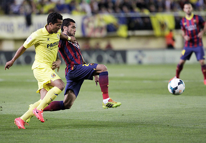 Barcelona's Dani Alves and Villarreal's Giovani Dos Santos vie for possession during their La Liga match at the Madrigal stadium in Villarreal on Sunday