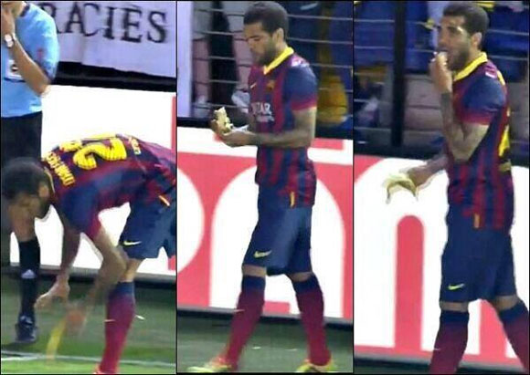 Barcelona's Dani Alves picks up and then eats the banana that was thrown at him during their match against Villareal on Sunday