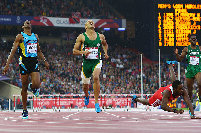 Cornel Fredericks of South Africa (centre) crosses the line ahead to win gold ahead of Jeffery Gibson of Bahamas and Jehue Gordon of Trinidad and Tobago in the Men's 400 metres hurdles final at Hampden Park on Thursday