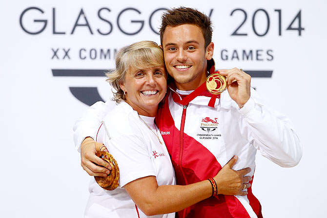 Tom Daley of England celebrates on the podium with his coach Jane Figueiredo after winning the Gold medal in the Men's 10m Platform Final at the Royal Commonwealth Pool on Saturday