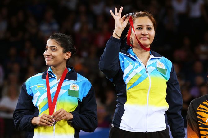 Silver medalists Ashwini Ponnappa and Jwala Gutta of India pose in the medal ceremony