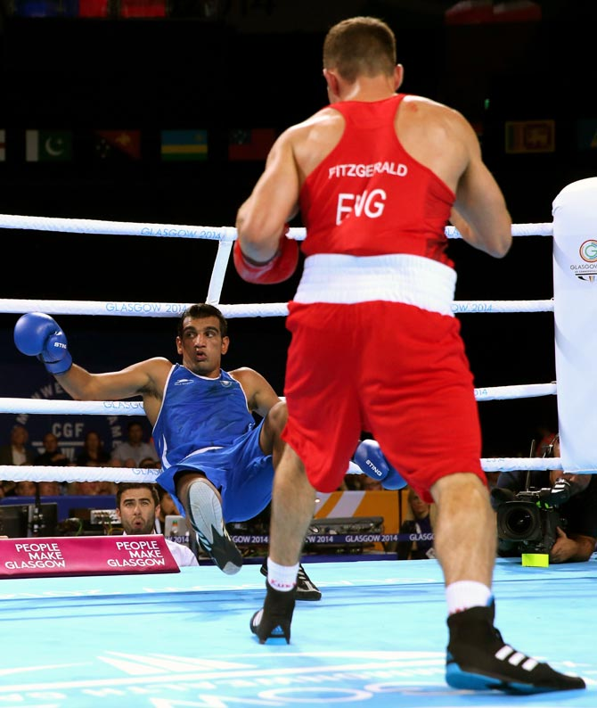 Scott Fitzgerald (red) of England knocks down India's Mandeep Jangra