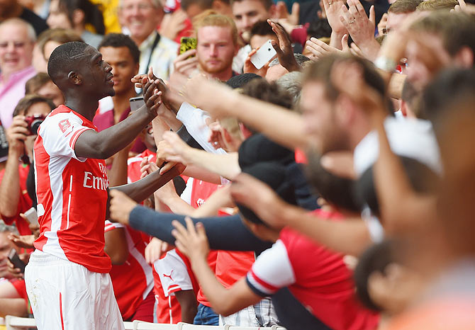 Yaya Sanogo of Arsenal celebrates scoring his 4th goal with fans during the Emirates Cup match between Arsenal and Benfica at the Emirates Stadium on Saturday