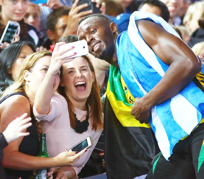 Usain Bolt of Jamaica greets fans as he celebrates winning gold in the Men's 4x100 metres relay final at Hampden Park on Day 10 of the Glasgow 2014 Commonwealth Games
