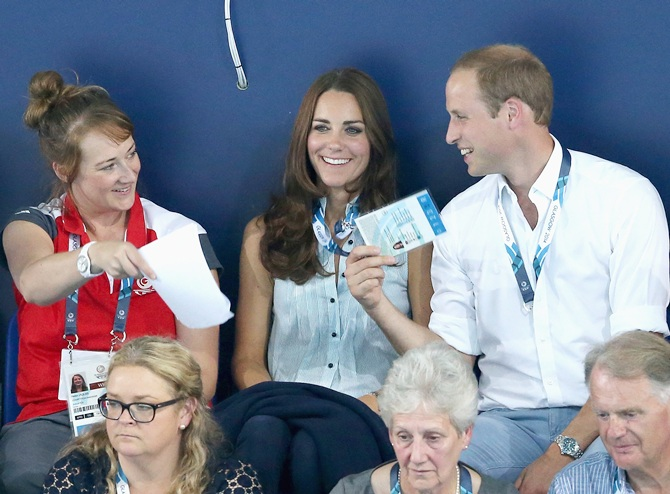Catherine, Duchess of Cambridge, is fanned in the heat of Tollcross Swimming Centre by Prince William, Duke of Cambridge, and a Games volunteer as they watch the swimming